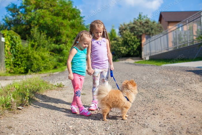 Two Little girls walking with small dog on a leash outdoor