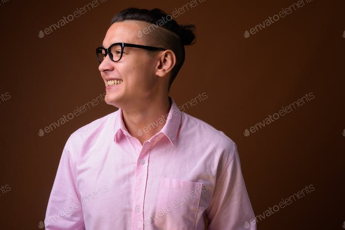 Young handsome multi-ethnic businessman against brown background