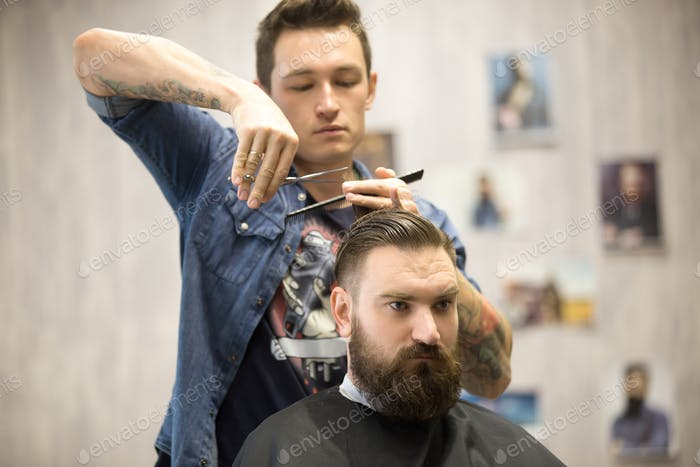 Hairstylist making haircut for male client