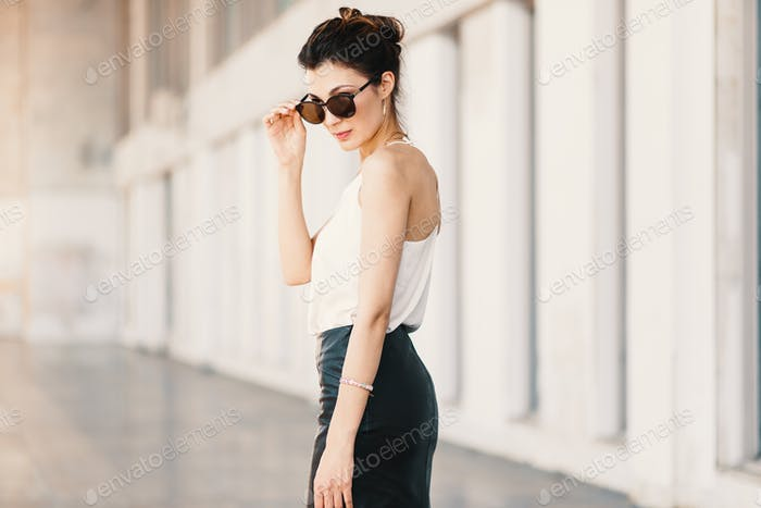Refined business woman holding fashionable sunglasses down looki