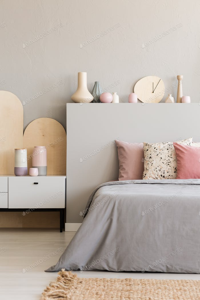 Pink pillows on grey bed with headboard in bedroom interior with