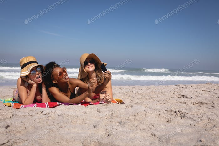 Women with hat and sunglasses taking selfie on the beach