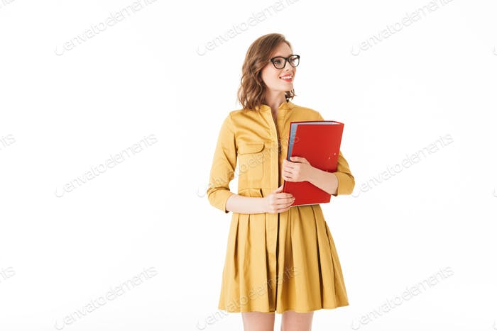 Smiling lady in eyeglasses and yellow dress standing with red folder in hand and looking aside