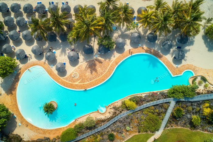 Aerial view of pool, umbrellas, sandy beach with green trees