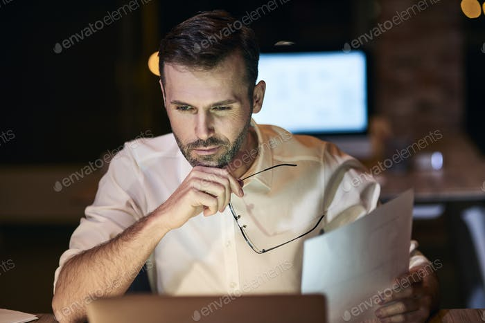 Focused man working late in his home office
