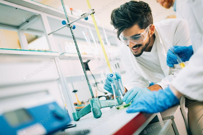 Young smiling student in white coat doing chemical tasks