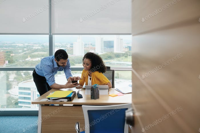 Business People Laughing In Office Watching Video Pictures On Smartphone