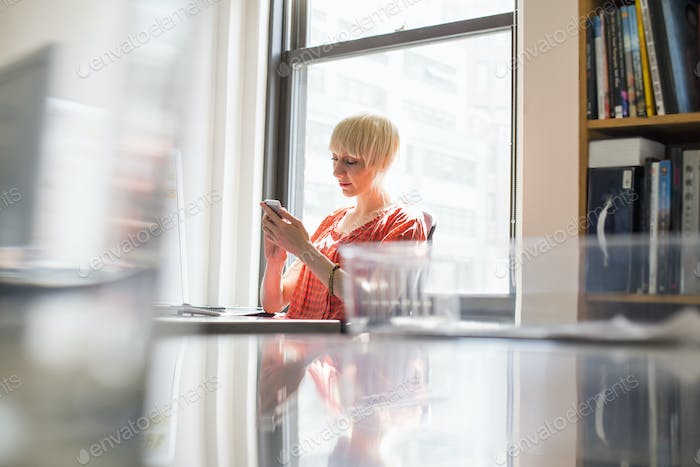 Office life. A young woman checking her cell phone.