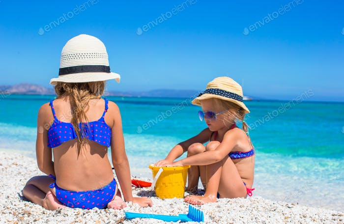 Little adorable girls playing with beach toys during vacation