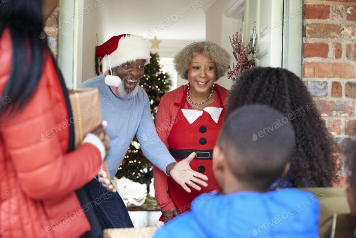 Grandparents Greeting Mother And Children As They Arrive For Visit On Christmas Day With Gifts