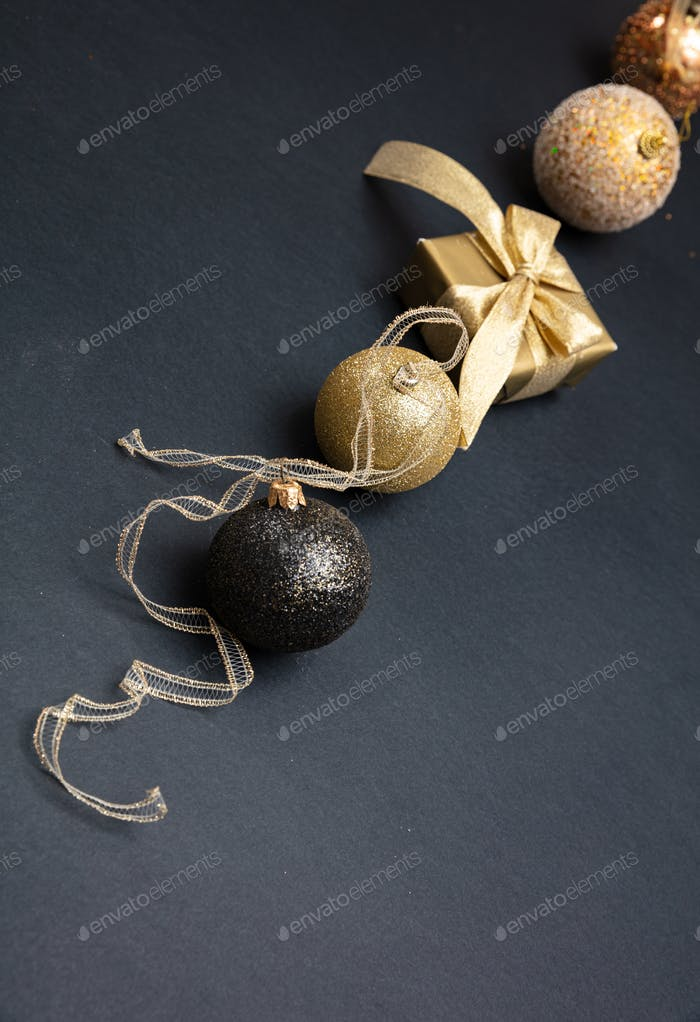 Xmas baubles shiny gold color against grey black background