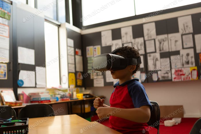 Cute schoolboy using virtual reality headset at desk in a classroom at elementary school