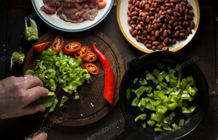 Man cuts green pepper for fajita top view