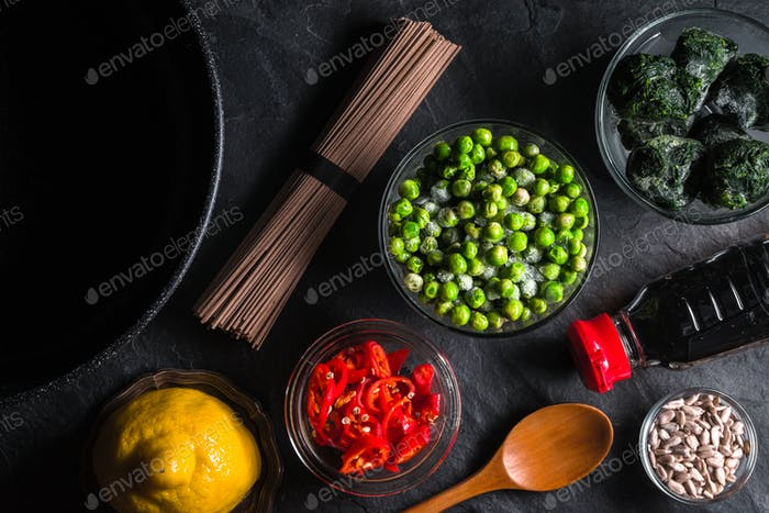 Sliced chili, frozen peas in a bowl of buckwheat noodles