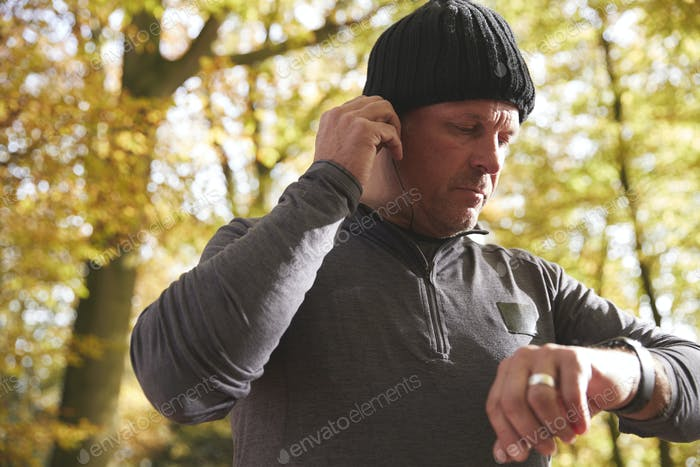 Man On Run Checking Activity Tracker And Putting In Earphones