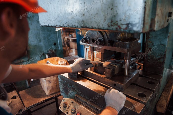 Old machine. Man in uniform works on the production. Industrial modern technology