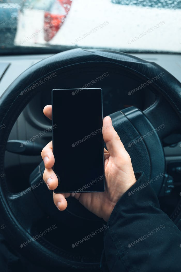 Man using smartphone in car