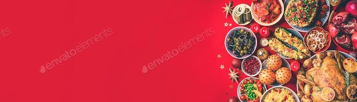 Festliches Familienessen. Draufsicht. Gebratenes Weihnachtshuhn mit Orangenscheiben, Preiselbeeren, Knoblauch