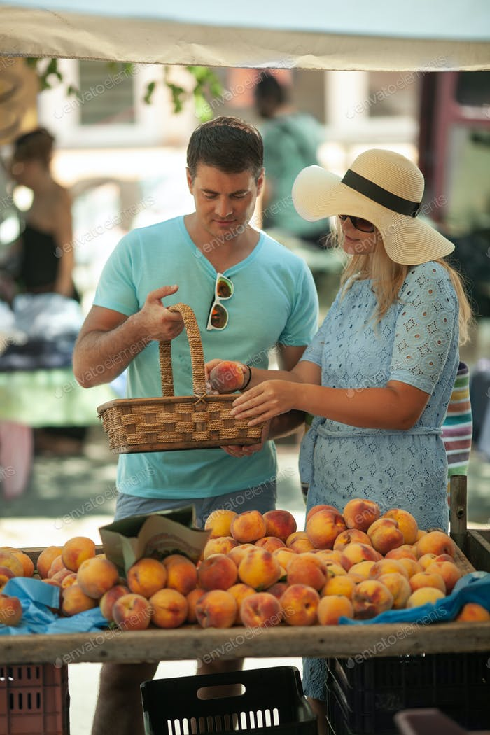 A couple getting peaches at the market