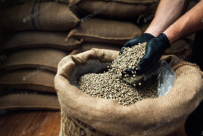 raw coffee pouring from a handful in a bag, against background of a warehouse, closeup side view