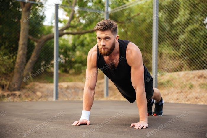Handsome bearded sportsman doing push-ups outdoors