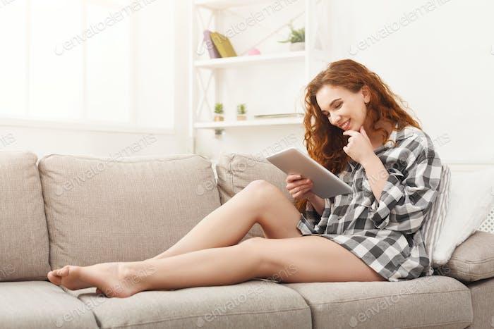 Glückliches Mädchen mit digitalem Tablet zu Hause