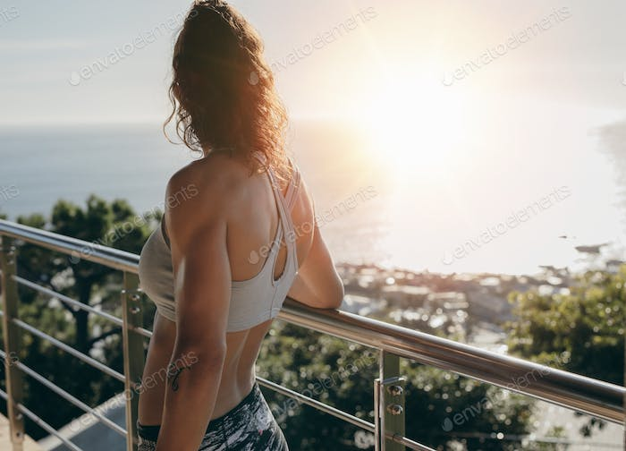 Woman standing by a railing in balcony and looking away