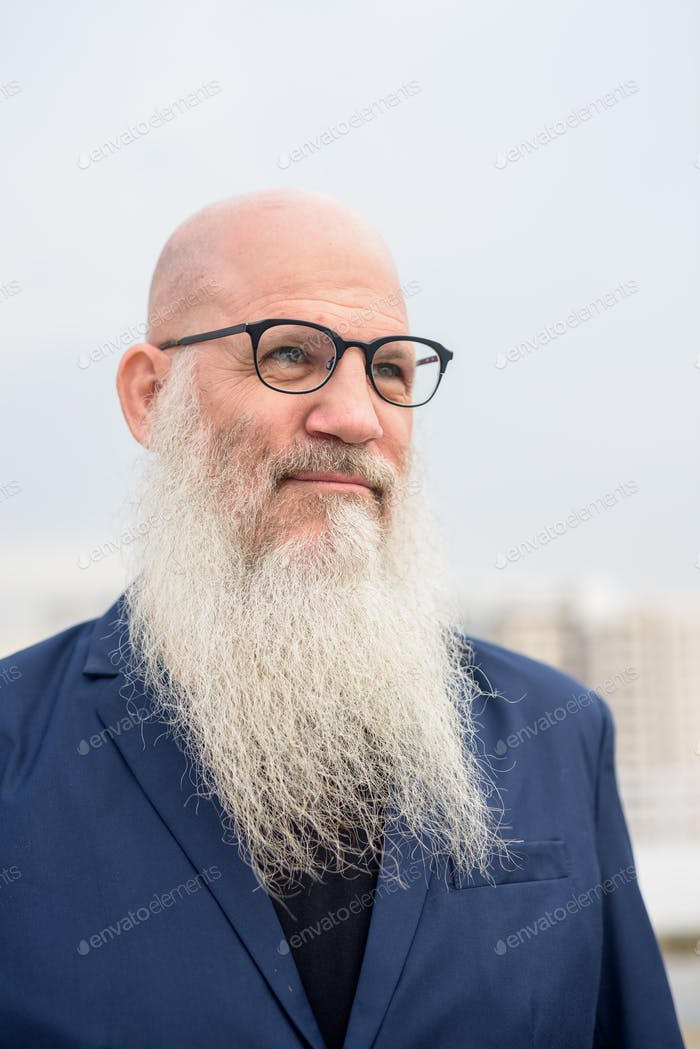 Face of mature bald bearded businessman with eyeglasses thinking outdoors