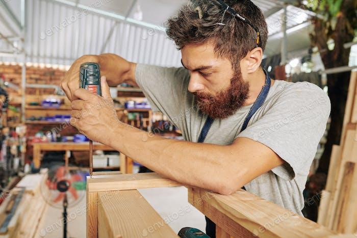 Carpenter assembling wooden stand