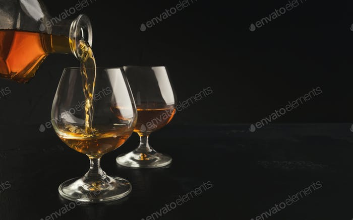Pouring brandy or cognac from bottle into glass