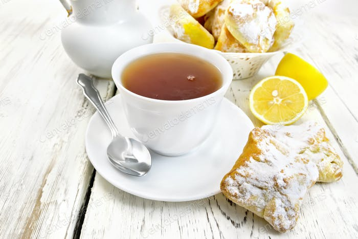 Tea in white cup with lemon cookies on board