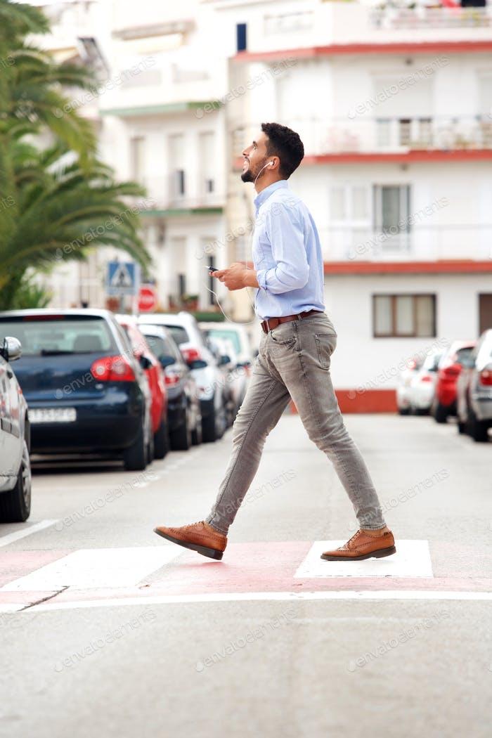 happy man crossing street with mobile phone