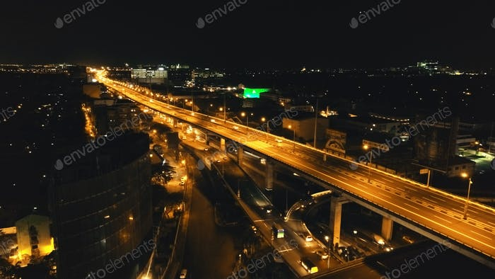 Closeup night traffic highway with driving cars, trucks aerial. Philippines Manila town cityscape