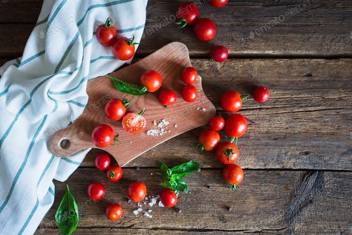 Frische Traubentomaten mit Basilikum und grobem Salz zur Verwendung als Kochzutaten auf Küchenbrett