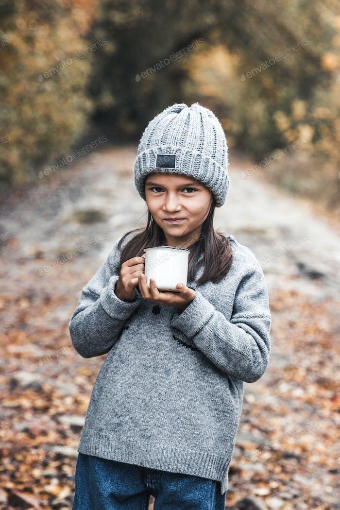 Little girl drinks tea in the autumn park