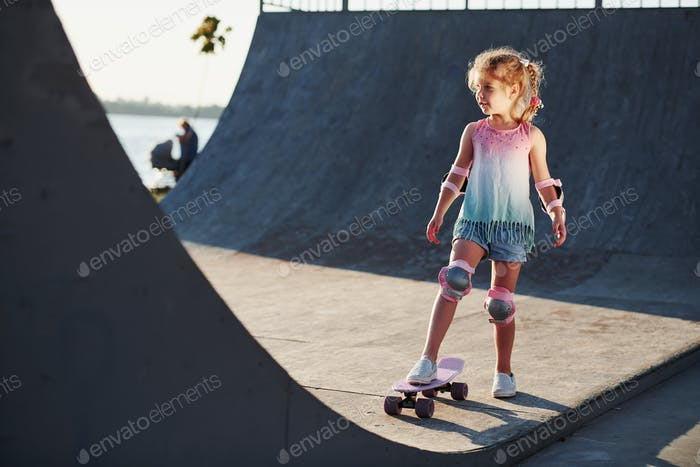 Sunny day. Little girl with scate on a ramp for extreme sports at daytime