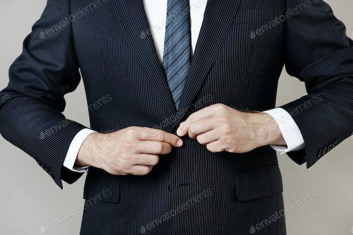 Hombre de negocios abotonando su traje