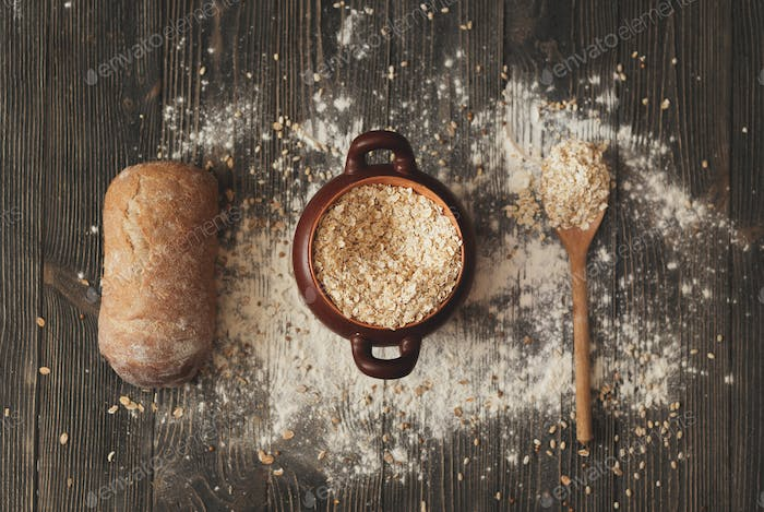 pot with  spoon cereals and bread on  rustic background. View from above.