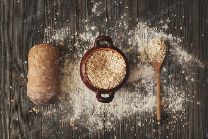 Topf mit Löffel Getreide und Brot auf rustikalem Hintergrund. Blick von oben.