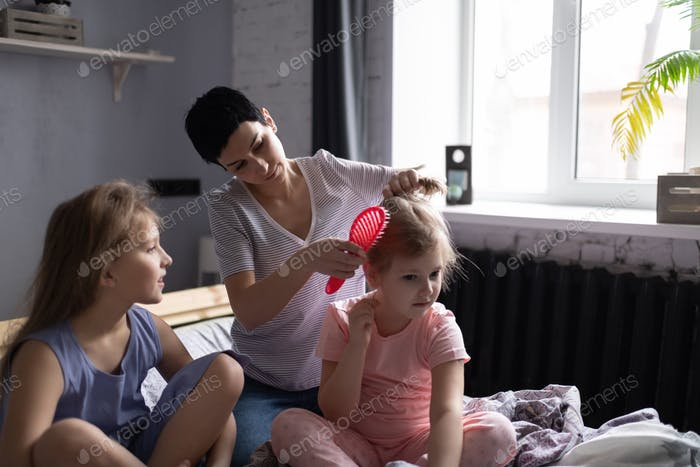 Mother doing hair of daughters in morning