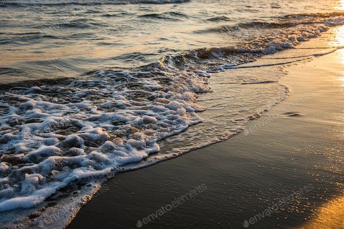 Wellen nähern sich dem Sandstrand während des goldenen Sonnenuntergangs