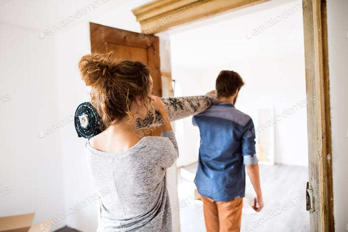 Young couple moving in new house, carrying a carpet.
