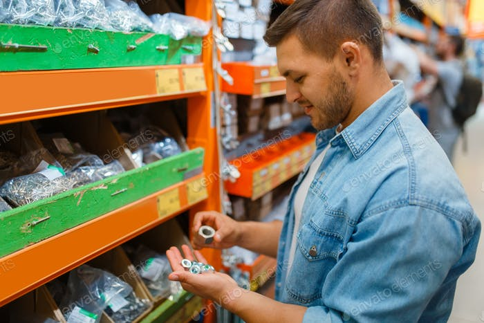 Male consumer choosing nuts in hardware store