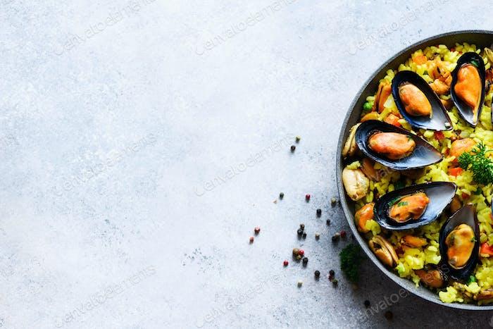 Traditionelle spanische Meeresfrüchte Paella in Pan Reis, Erbsen, Garnelen, Muscheln, Tintenfisch auf hellgrauem Beton