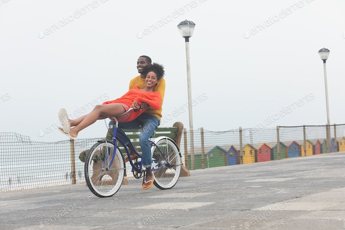 Front view of cute Multi-ethnic couple enjoying at bicycle while riding at pavement on sunny day
