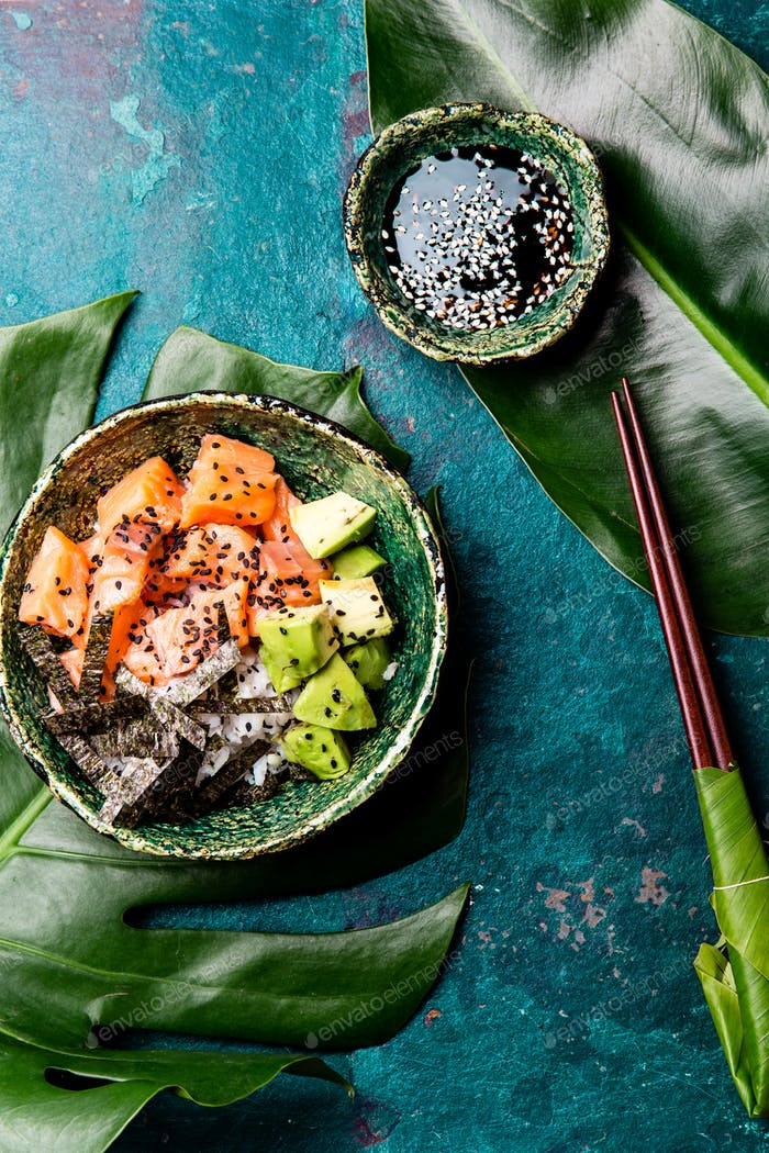 Hawaiian salmon poke poce with avocado, rice and sesamo served in bowls on tropical leaves