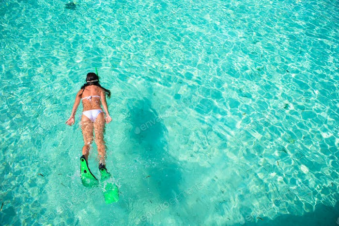 Young woman snorkeling in tropical water on vacation