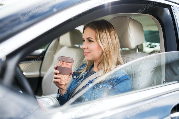 Young woman driver sitting in car, drinking coffee.