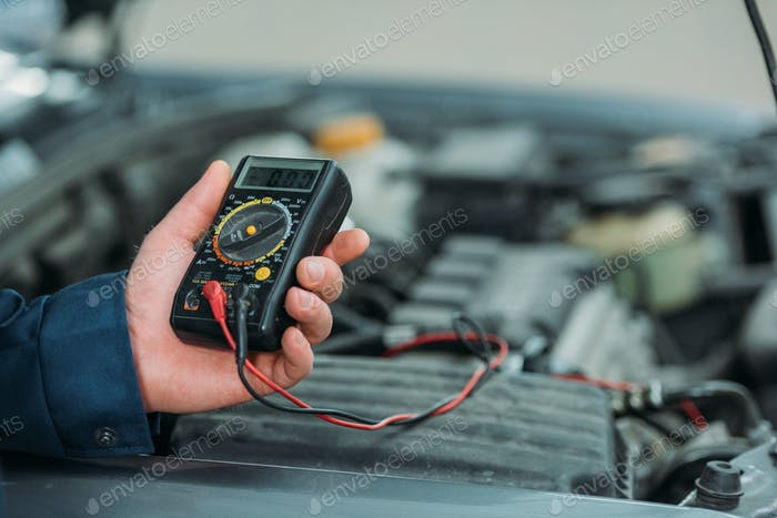 Cropped shot of automechanic using a digital multimeter in a service workshop.