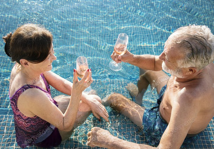 Senior couple drinking prosecco in a swimming pool